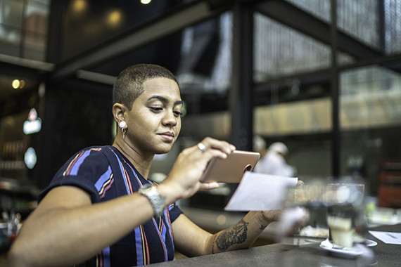Woman holding phone taking picture of check